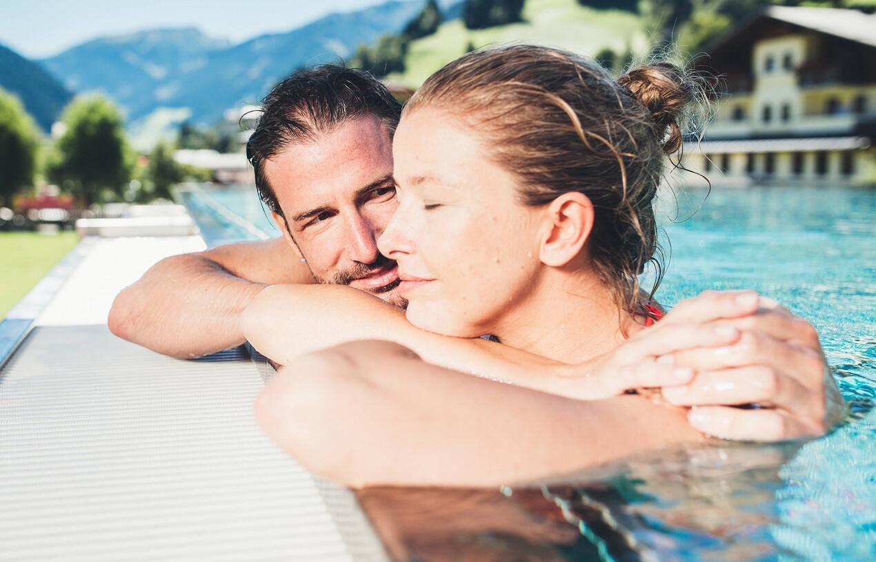 Paar beim Baden im Außenpool vom  Wellnesshotel Nesslerhof in Großarl