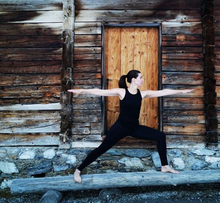 Yogalehrerin Verna bei Yogaübung Krieger II auf Holzbalken - Urlaub mit Yoga im Salzburger Land.