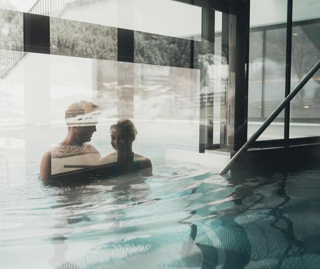 Pärchen beim Baden im beheizten Außenpool im Winterurlaub im 4-Sterne Superior Wellnesshotel Nesslerhof, Großarl