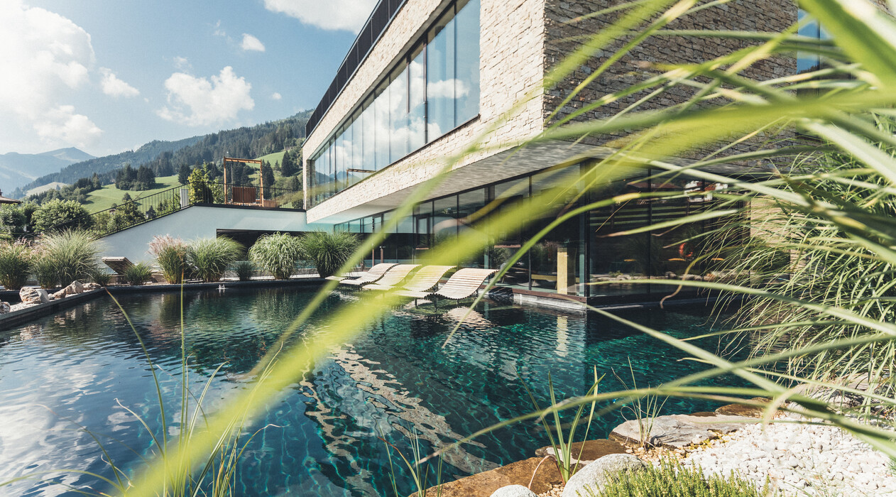 Außenpool mit schwebenden Doppelliegen aus Holz im großzügigen Garten des 4-Sterne Superior Wellnesshotels Nesslerhof in Großarl, Salzburger Land