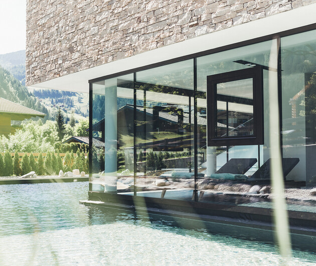 Außenpool und Entspannungsliegen im 4*S Wellnesshotel Nesslerhof im Salzburger Land
