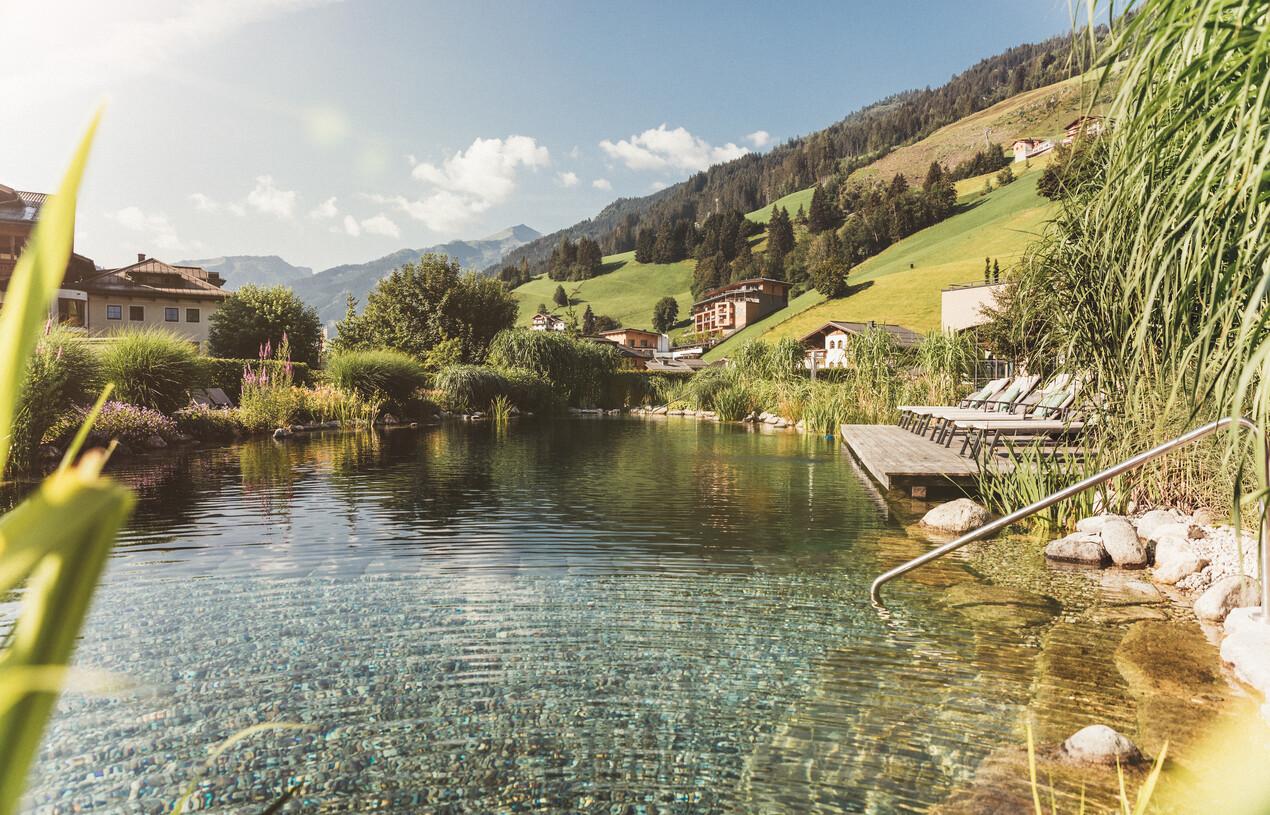 Großer Naturbadeteich mit gemütlichen Liegen im 4*S Wellnesshotel Nesslerhof, Großarl.
