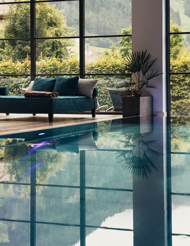 Indoorpool mit gemütlicher Doppelliege und Blick in den Hotelgarten im 4*S Wellnesshotel Nesslerhof in Großarl, Salzburger Land