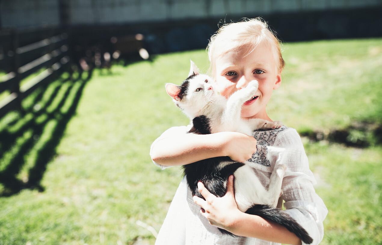 Mädchen hält eine Katze im Familienhotel Nesslerhof im Salzburger Land