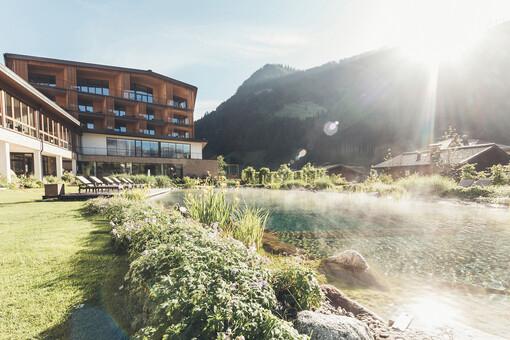 Sommerliche Außenansicht vom Wellnesshotel Nesslerhof mit Naturbadeteich im Salzburger Land