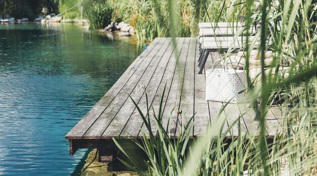 Badesteg mit bequemen Liegen am Ufer des Naturbadeteich in der großen Badelandschaft des Wellnesshotel Nesslerhof im Salzburger Land.