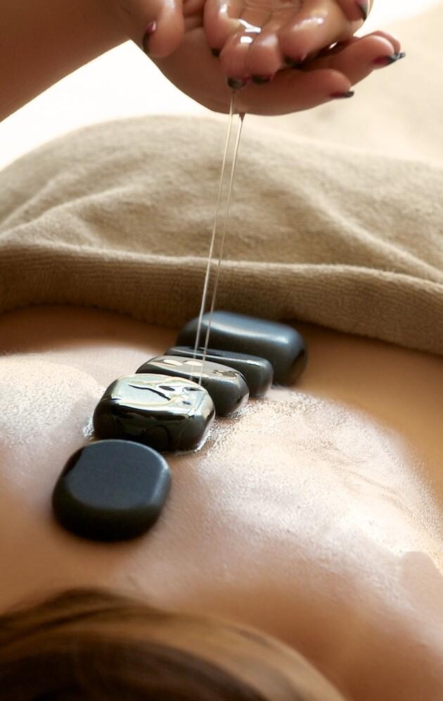 Frau bei entspannender Hot Stone Massage im Urlaub im Wellnesshotel Nesslerhof.