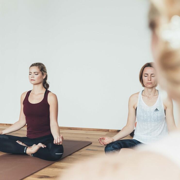 Damen im Schneidersitz beim Yoga im Urlaub in Großarl