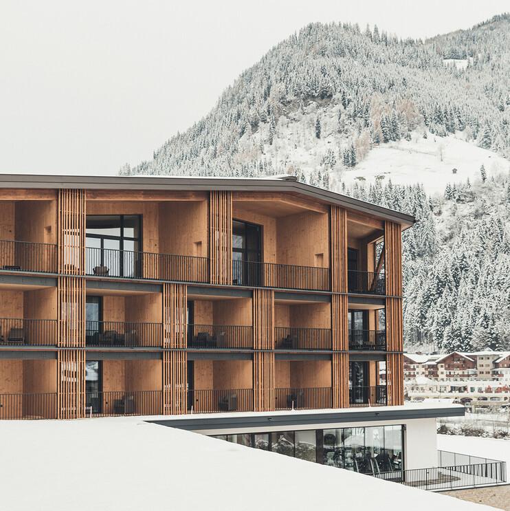Blick auf die großzügigen Zimmer mit Balkon und die herrliche verschneite Winterlandschaft rund um das 4*S Ski- & Wellnesshotel Nesslerhof in Großarl, Salzburger Land