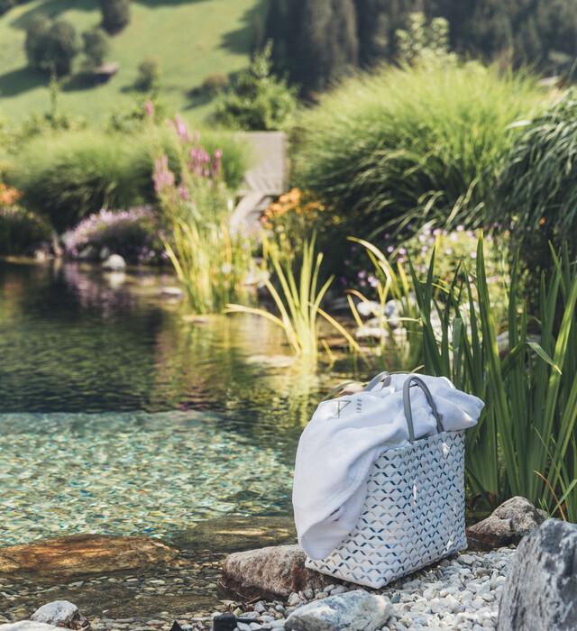 Badetasche am Ufer des Naturschwimmteich im 4*S Wellnesshotel Nesslerhof im Salzburger Land.