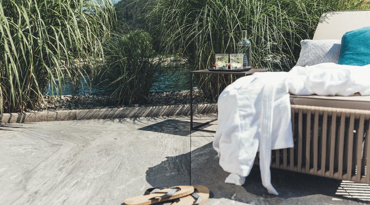 Bequeme Liege mit Bademantel beim Naturschwimmteich im 4*S Wellnesshotel Nesslerhof in Großarl, Salzburger Land