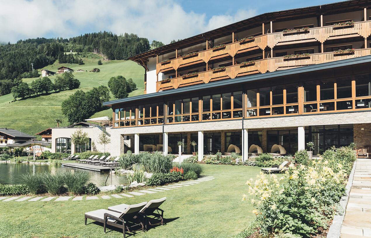 Großzügige Liegewiese mit Liegen vor dem Naturschwimmteich im 4*S Wellnesshotel Nesslerhof in Großarl, Salzburger Land