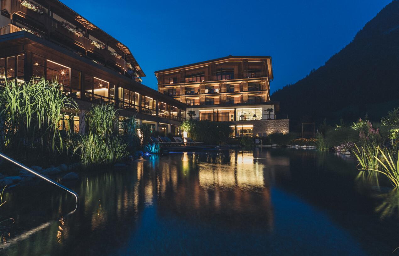 AUßenansicht am Abend mit Naturschwimmteich des 4*S Hotel Nesslerhof in Großarl, Salzburger Land