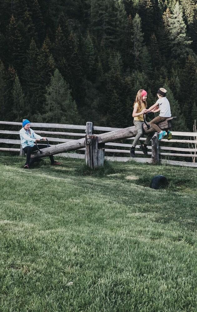 Kinder auf einer Holzwippen im Großarltal - perfekter Familienurlaub im 4*S Hotel Nesslerhof im Salzburger Land