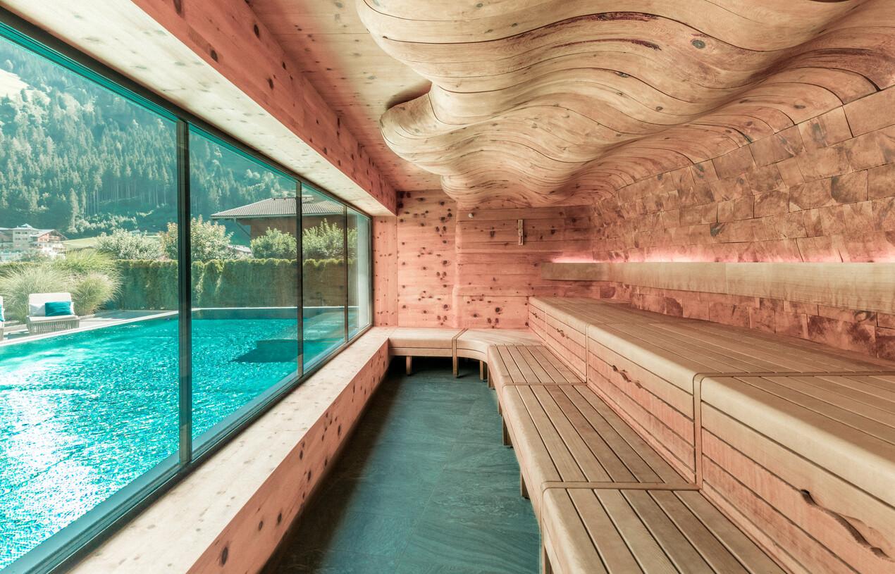 Zirbensauna mit Panoramablick auf den Außenpool der großen Wasserwelt im 4*S Wellnesshotel Nesslerhof, Salzburger Land.