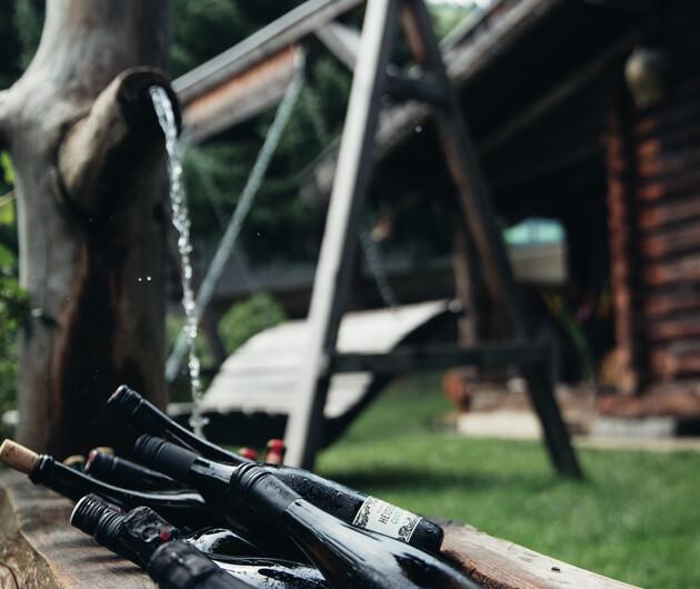 Weinflaschen eingekühlt in Holzbrunnen vor der Nessleralm