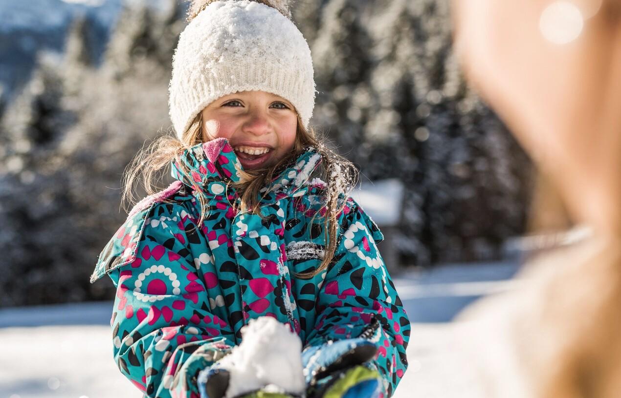 Mädchen im bunten Skianzug beim Spielen im Schnee - perfekter Familienurlaub im 4-Sterne Superior Hotel Nesslerhof in Großarl, Salzburger Land