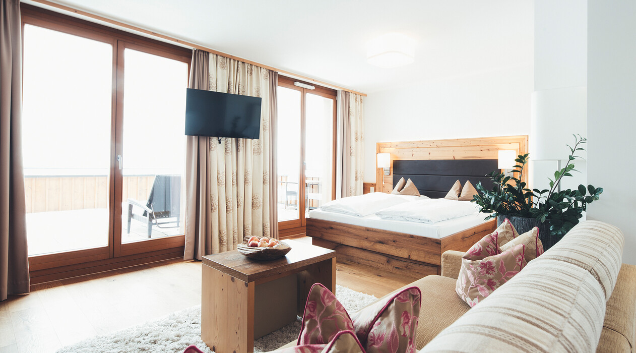 Gemütliches Doppelbett, Panoramafenster, Balkon und Couch in der Familiensuite Wunderkind im Hotel Nesslerhof