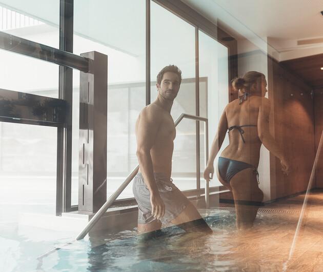 Paar steigt aus dem Pool der großen Badelandschaft vom Wellnesshotel Nesslerhof im Salzburger Land