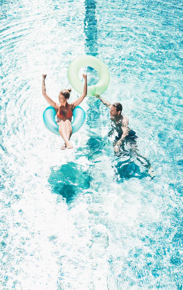 Paar mit Schwimmreifen im Außenpool der großen Badelandschaft vom Wellnesshotel Nesslerhof im Salzburger Land