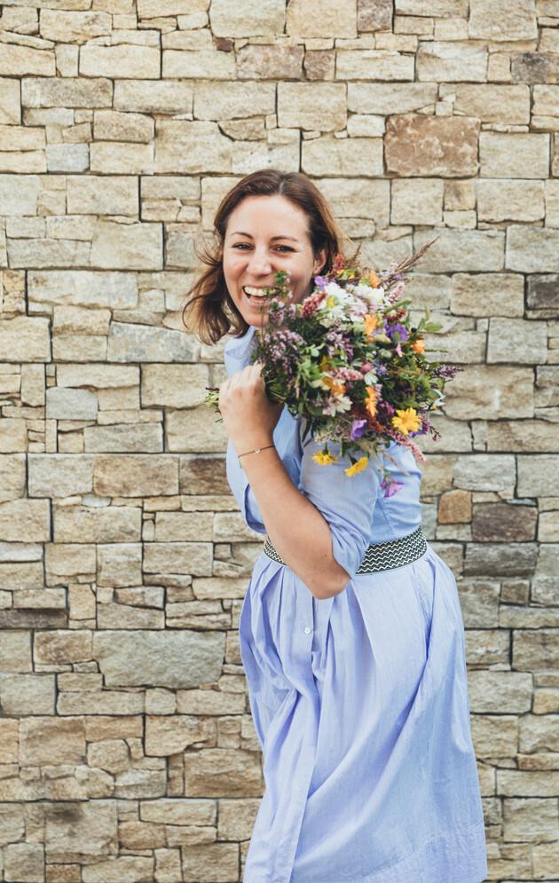 Tina Neudegger mit Blumenstrauß, Ihre herzliche Gastgeberin im 4*S Hotel Nesslerhof in Großarl, Salzburger Land
