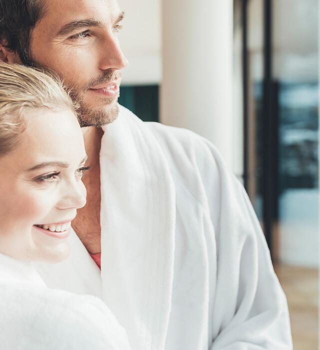Paar in Bademänteln im Wellnessurlaub im Salzburger Land