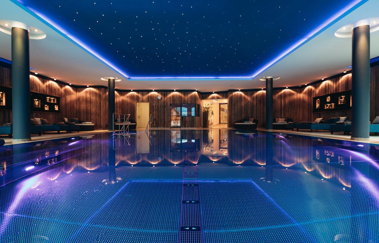 Indoor-Pool mit Sternenhimmel und gemütlichen, großzügigen Liegen im 4*S Wellnesshotel Nesslerhof in Großarl, Salzburger Land