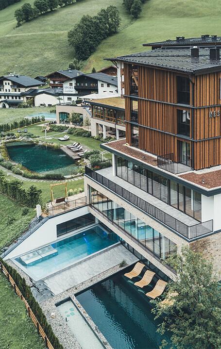 Außenansicht von oben des 4*S Hotel Nesslerhof in Großarl mit Naturschwimmteich und Außenpools