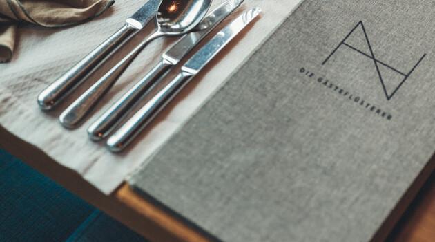 Schön gedeckter Tische mit Weingläsern und Kerzen im Restaurant des Hotel Nesslerhof in Großarl.