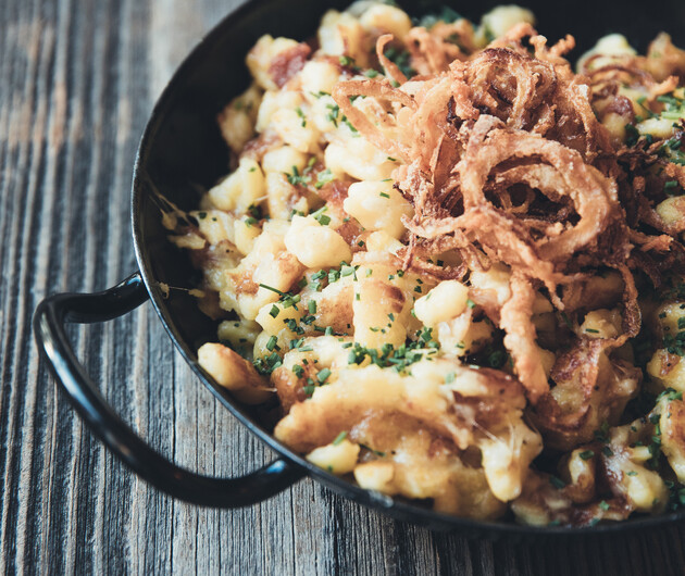 Frisch zubereitete Kasnocken mit Röstzwiebeln in schwarzer Pfanne im Gourmethotel Nesslerhof in Großarl.