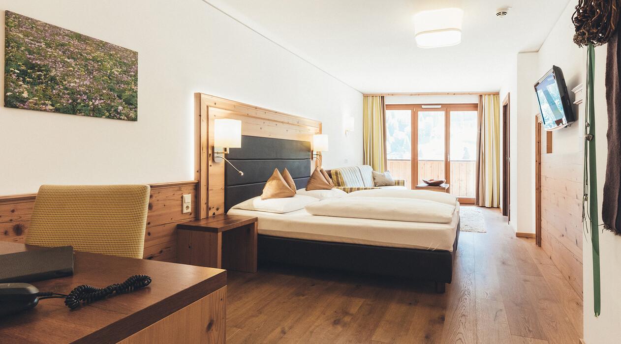 Großzügige Suite mit Doppelbett und moderner Ausstattung, Holzfußboden und Balkon im Hotel Nesslerhof, Großarl