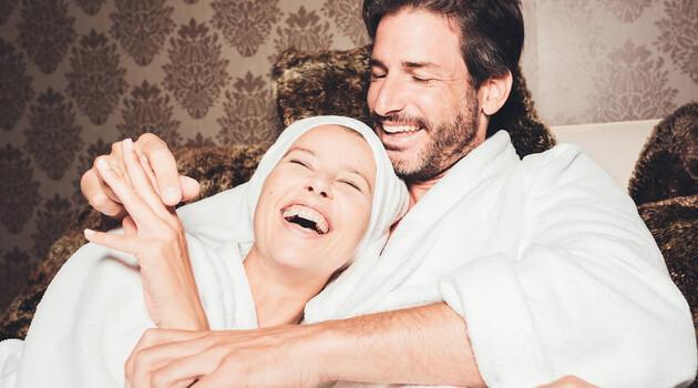 Lachendes Paar in Bademänteln im 4* Wellnesshotel Nesslerhof im Salzburger Land