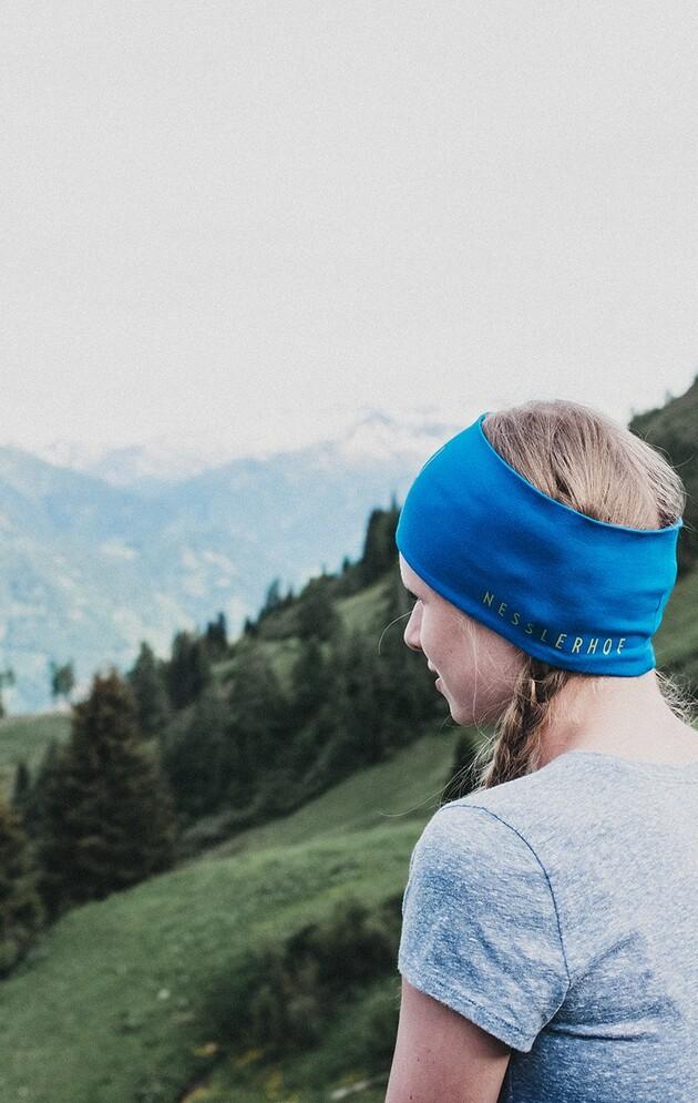 Mädchen mit Nesslerhof-Stirnband und Panoramablick auf die umliegenden Almen.