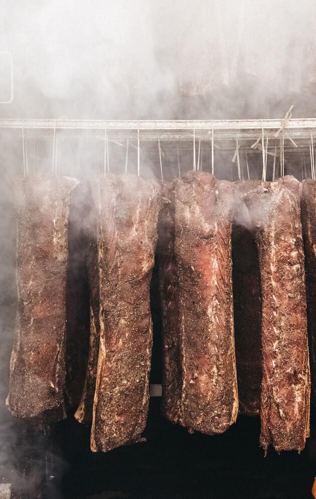 Frisch geräucherter Speck im Räucherofen aus der hauseigenen Metzgerei.