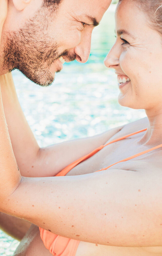 Lachendes Paar im Badeteich der großen Badelandschaft vom Wellnesshotel Nesslerhof im Salzburger Land