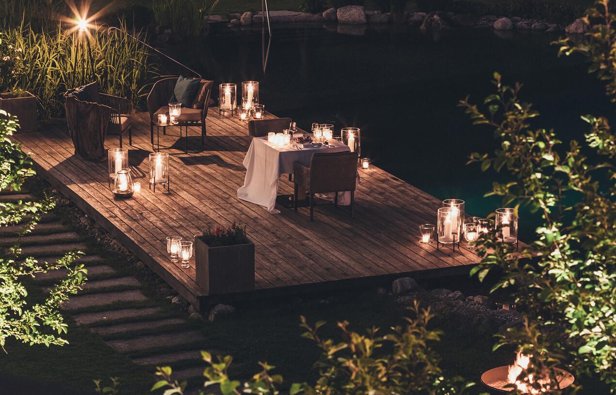 Gedeckte Tische für Candle-Light-Dinner am Ufer beim romantischen Wellnesshotel Nesslerhof im Salzburger Land