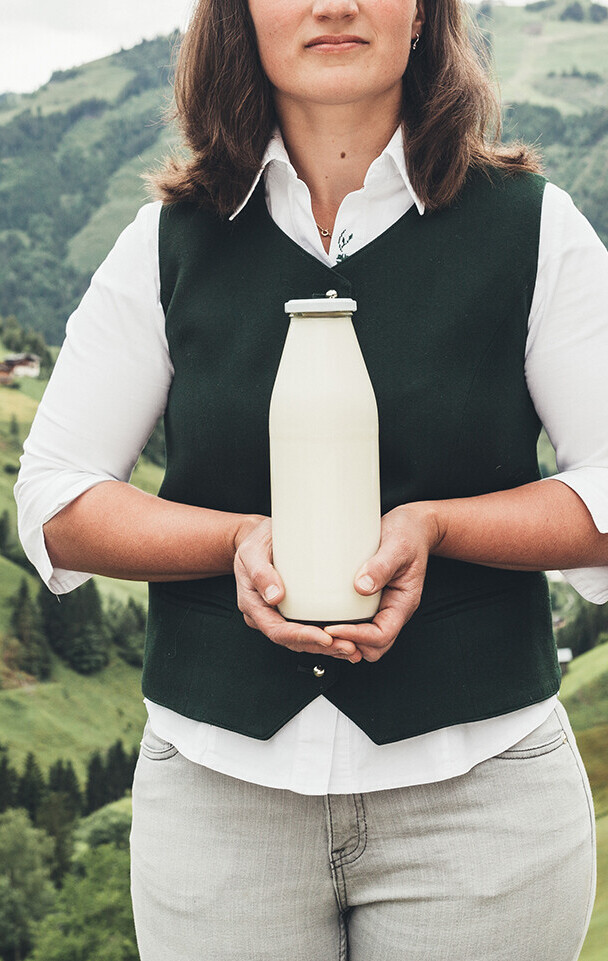 Produkte aus der Region im Genießerhotel Nesslerhof: Bäuerin mit Milchflasche.
