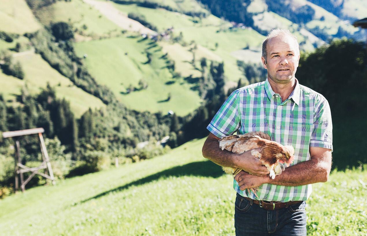 Eier aus der Region für das Gourmethotel Nesslerhof: Landwirt mit Henne auf einer Alm in Großarl.