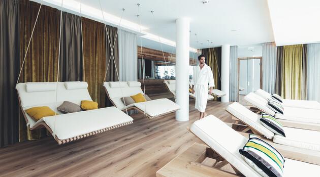 Junger Mann im Bademantel spaziert durch den Ruhebereich im Wellnesshotel Nesslerhof in Großarl